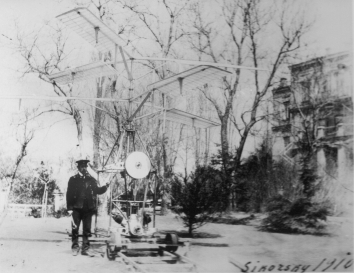 1910. AA. Kyiv, Ukraine. Igor Sikorsky with H-2 (second helicopter prototype) in the backyard of the Sikorsky Family house at 15Б Yaroslaviv Val Street, Kyiv, Ukraine.  A copy of the photograph is posted in the U.S. Embassy in Ukraine building at 4 Aviaconstructor Igor Sikorsky Street, Kyiv, Ukraine. Provided by the Sikorsky Family and Robert Homans.